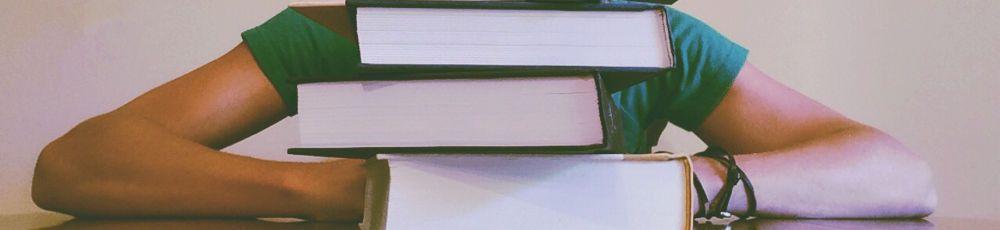 Studierende vor einem Bücherstapel
